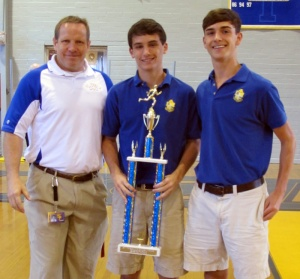 Zachary Albright and Don Lipani present Athletic Director Craig Ketelsen with the Parish trophy.
