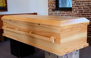 Saint Joseph Woodworks offers two kinds of caskets. The Monastic style is a basic cypress flat top casket with metal handles on the side (Cost: $1500). The Traditional style (as shown above) is a cypress curved top casket with wooden handles on each side (Cost: $2000)