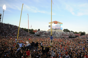 Ole Miss fans storm the field after the Rebels dramatic win over the Alabama Crimson Tide. In the process of tearing down the fist goalpost. (Photo Credit: CBS Sports)