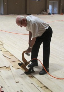 Retired Christian Brother, Alfred Baltz, a longtime resident and former faculty member and athletic director for SPS, nails floorboards in place on the new basketball court. Bro. Alfred was instrumental in building many campus structures including the old gym and Horack and Booth Pavilions. (photo by Karen Hebert)