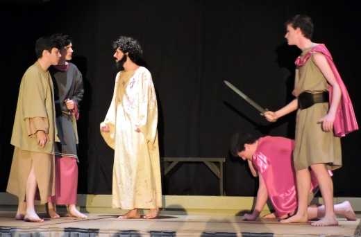 Jesus (Spencer Albright) prepares to be taken into custody by two Roman soldiers (Patrick Stewart, Nick Oubre) as he sees of his disciples (Addison Nick, Shane Davies).