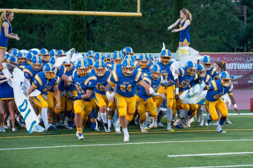Wolves break through the banner to start the home game against Jesuit, earlier this season. (photo by: Joey Michel)