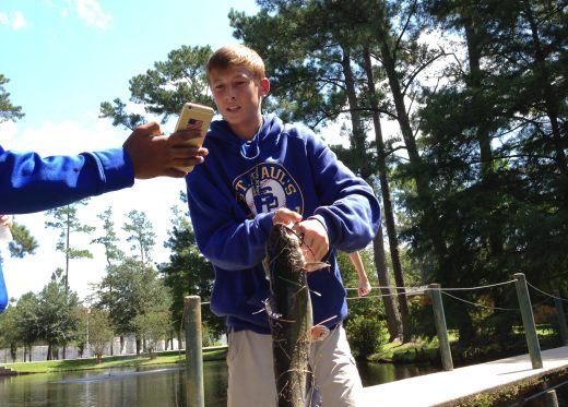 Freshman Dominick O'Brien catches a catfish from pond. (Photo by Tyler Petro)