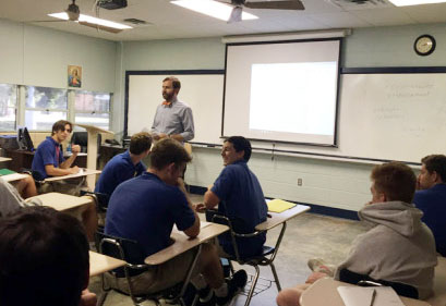 Roger Bacon, the new religion IV teacher, talking to students about their reflection assignment. (Photo by Ethan Hopel)