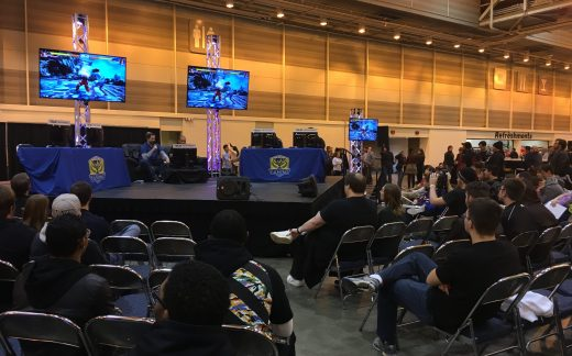 A group of attendees spectates a Street Fighter V tournament.