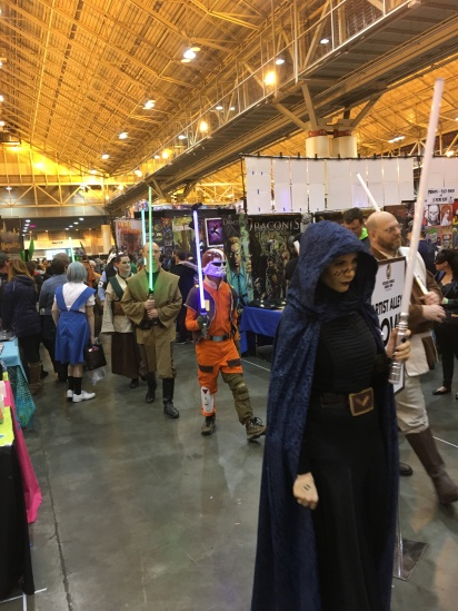 A large crowd of Star Wars cosplayers march through the hall.