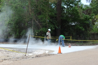 Construction workers work on the parking lot driveway.
